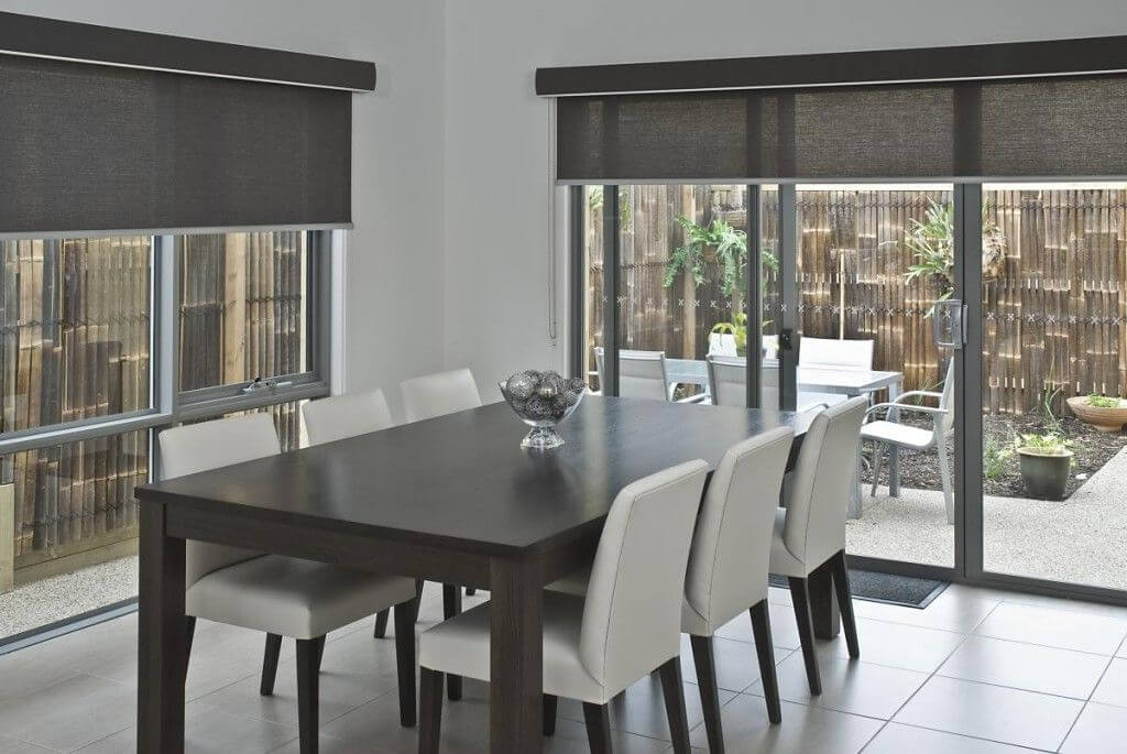 Dark dining table with black roller blinds with view to outdoor dining