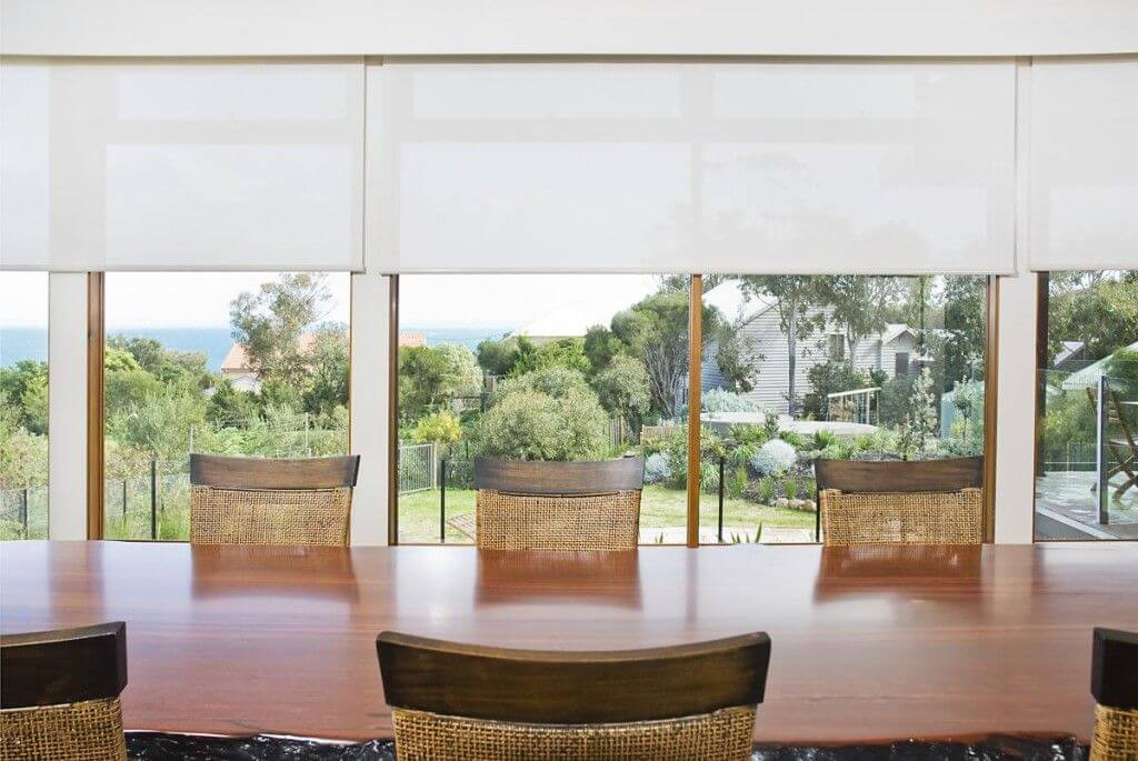 white roller blinds behind wooden table