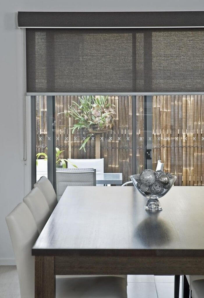 view to outdoor dining from behind indoor table with black roller blinds