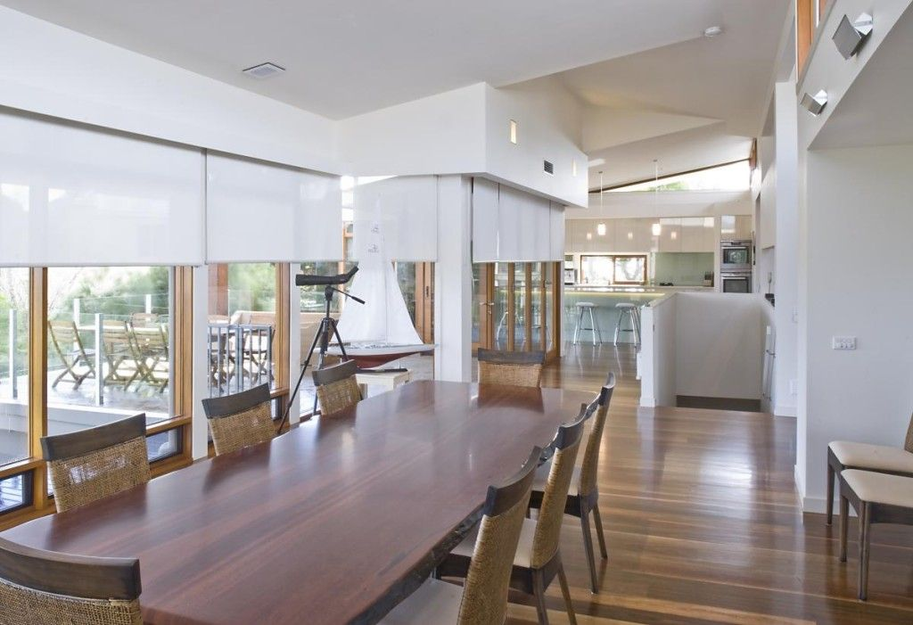 large timber table in living room with white roller blinds